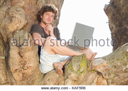 Pensive man using laptop in tree Banque D'Images