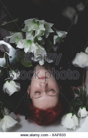 L'adolescence, relaxant immergé dans l'eau avec des roses blanches, romance scen Banque D'Images