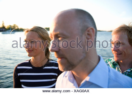 Trois personnes debout près de l'eau, Fejan, archipel de Stockholm, Suède.
