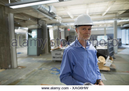 Portrait confiant architecte en hard-hat construction site Banque D'Images