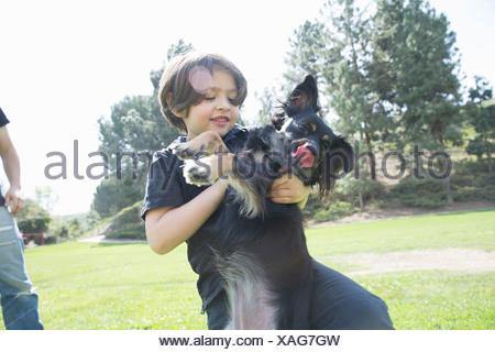 Jeune garçon dans le parc à jouer avec son chien Banque D'Images