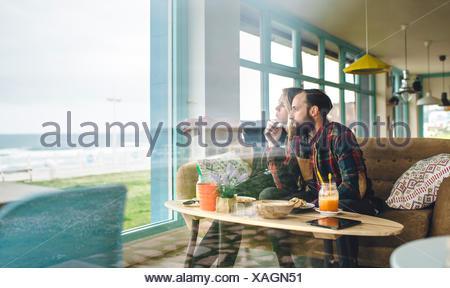 L'Espagne, les Asturies, Couple appréciant les marins à travers la fenêtre du café tout en ayant un brunch Banque D'Images