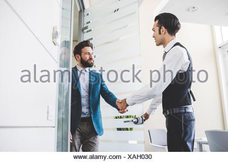 Jeune homme d'affaires et le client shaking hands in office Banque D'Images