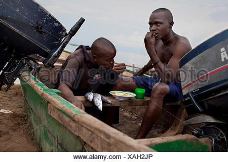 Les jeunes pêcheurs assis dans un bateau sur la plage de sable de prendre leur petit déjeuner après une nuit de travail, le Burundi, Nyanza-lac, Mvugo, Nyanza Lac Banque D'Images