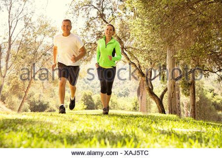 Mature couple running through park Banque D'Images