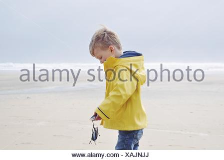 Boy standing on beach in raincoat holding moules fraîches Banque D'Images