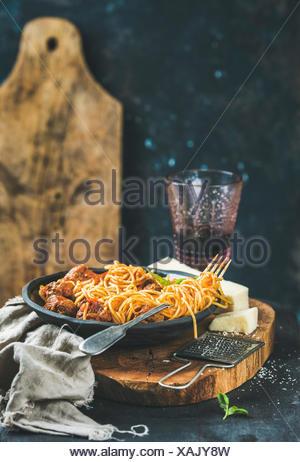 Dîner de pâtes italiennes. Spaghetti avec meatballas, basilic et parmesan dans la plaque noire et le vin rouge dans le verre au bord rustique en bois, bleu foncé wa Banque D'Images