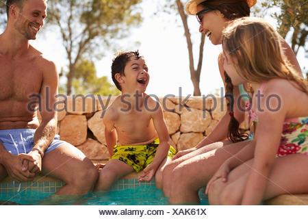 Famille en vacances de détente au bord de piscine extérieure Banque D'Images
