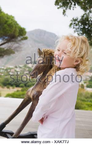 Jeune fille jouant avec un cheval à bascule Banque D'Images