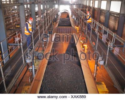 L'observation des travailleurs dans des camions de charbon mondial Banque D'Images
