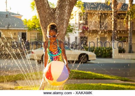 Fille avec beachball en jardin réseau sprinkleur Banque D'Images