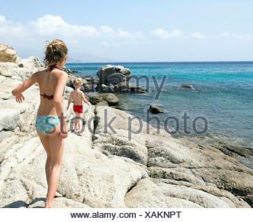 Jeune fille et un jeune garçon marcher sur des roches par l'eau. Banque D'Images