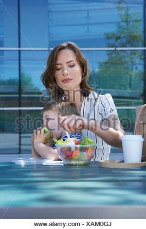 Businesswoman et son fils sur la table en face de bureau en dehors elle mange de la salade pour aller manger son fils apple. Banque D'Images