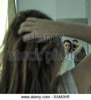 Man Photographing Woman avec la main dans les cheveux tout en réfléchissant sur le miroir à la maison Banque D'Images
