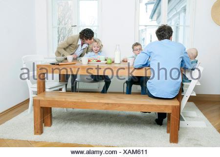 Famille à la table du petit déjeuner dans la cuisine Banque D'Images