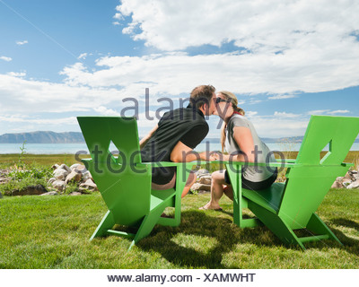 Young couple sitting on meadow et Baisers Banque D'Images