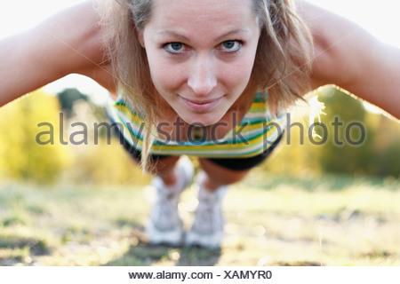 Jeune femme faisant pousser ups