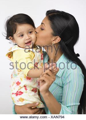 Mère indienne, baiser sur la joue de la petite fille monsieur#702O;702L Banque D'Images