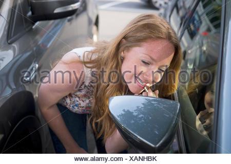 Young woman applying lipstick tandis qu'à la voiture en miroir du vent Banque D'Images