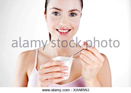Une jeune femme de manger un yaourt Banque D'Images
