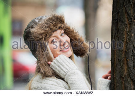 Portrait of beautiful young woman wearing fur hat outdoors Banque D'Images