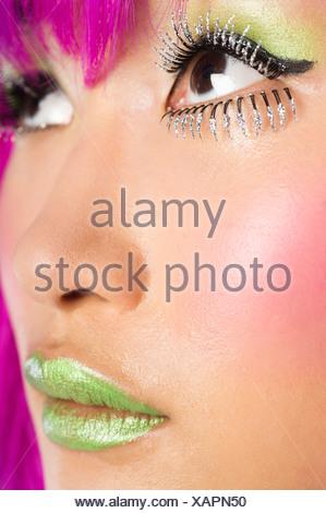 Jeune femme extrême funky le visage de faux cils rouge à lèvres vert Banque D'Images