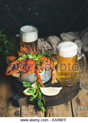 Deux pintes de bière de froment et d'écrevisses bouillies avec du citron et du persil sur dark tour servant au fond en bois rustique, se Banque D'Images