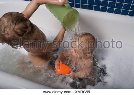 Garçon verser de l'eau plus de petit frère Banque D'Images