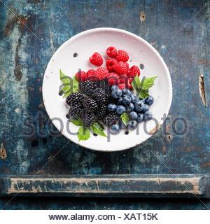Mélange de baies fraîches avec les feuilles dans une passoire en céramique vintage sur fond de bois bleu Banque D'Images