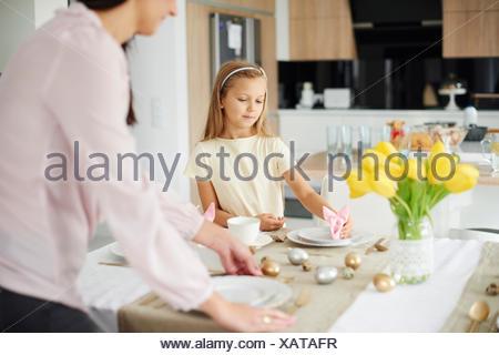 Mère et fille la préparation placez les paramètres à Pâques, table à manger Banque D'Images