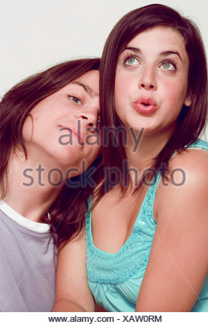Teenage couple sitting close, femme longue ligne droite cheveux brunette wearing blue sequinned vest looking up et de côté à la recherche de Banque D'Images