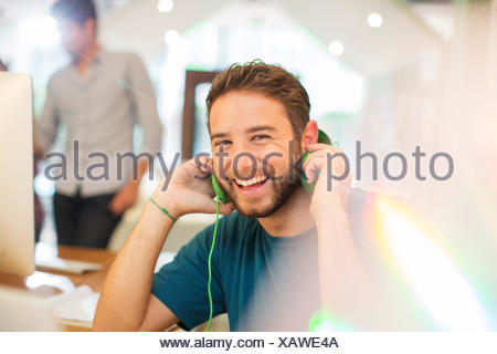 Portrait créatif enthousiaste businessman listening to headphones in office Banque D'Images