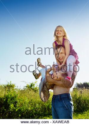 Père jouant avec ses filles à l'extérieur Banque D'Images