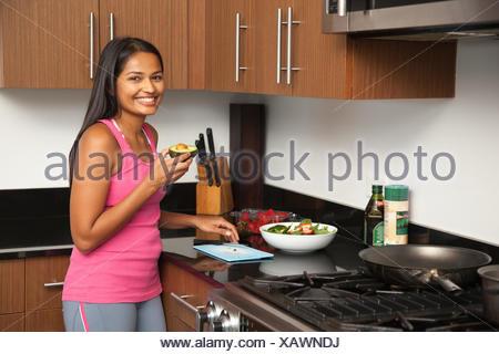 Woman preparing salad in kitchen Banque D'Images