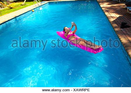 Fille sur le lit gonflable dans la piscine Banque D'Images