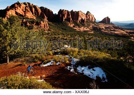 Un homme d'âge moyen chevauche son vtt à travers la roche rouge, près de Sedona, AZ. Banque D'Images