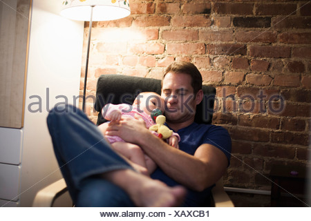 Père holding baby daughter in armchair Banque D'Images