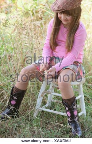 Jeune fille assise sur un tabouret de porter un chapeau et des bottes de cow-boy; Troutdale, Oregon, United States of America Banque D'Images