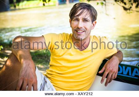 L'homme se détend au bord de la rivière, portrait, contreforts des Alpes, Bavière, Allemagne Banque D'Images