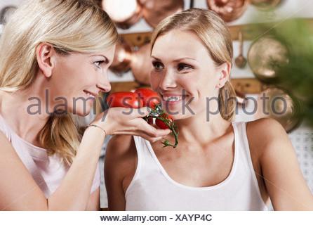 Italie, Toscane, Magliano, deux jeunes femmes avec des tomates dans la cuisine, smiling Banque D'Images