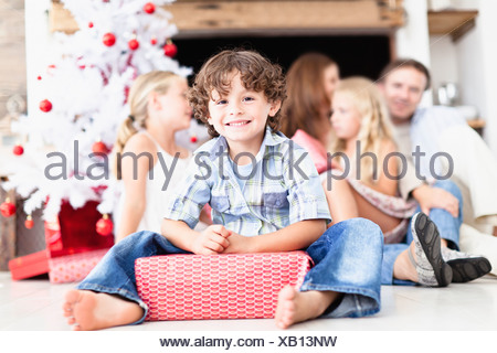 Boy sitting with wrapped Christmas Gift Banque D'Images