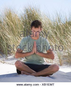Jeune homme performing yoga sur une plage Banque D'Images