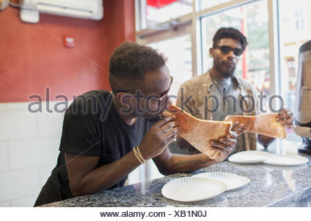 Deux jeunes hommes de manger des pizzas.
