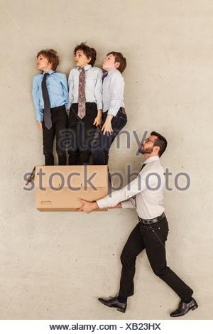 Businessman Holding boîte en carton tandis que les garçons de prendre l'avion Banque D'Images