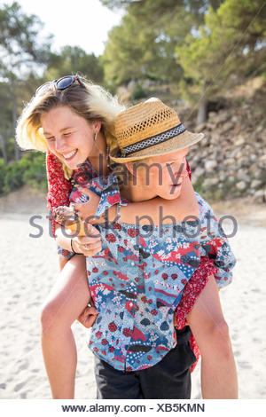 Man on beach donnant smiling woman piggyback, Majorque, Espagne Banque D'Images
