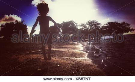 Silhouette de Boy Jumping At Beach Banque D'Images