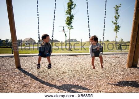 Deux garçons assis sur des balançoires Banque D'Images