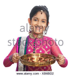 Fille imitant comme woman holding lampes à huile et smiling on diwali Banque D'Images