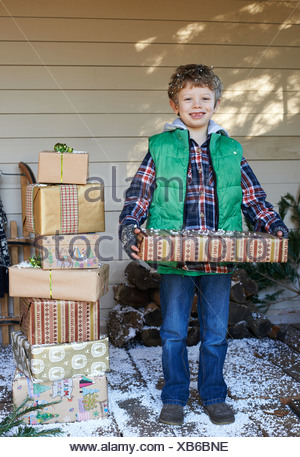 Boy holding Christmas gifts on snowy porch Banque D'Images