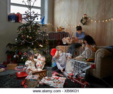 Frères et sœurs d'ouvrir les cadeaux de Noël dans la salle de séjour Banque D'Images